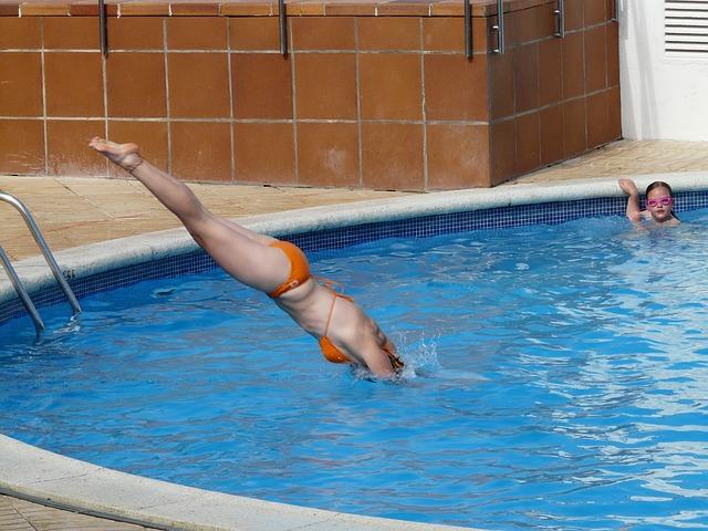 žena skáče do bazénu
